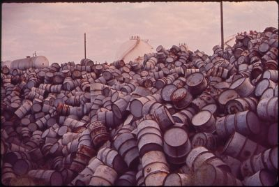 1280px-A_MOUNTAIN_OF_DAMAGED_OIL_DRUMS_NEAR_THE_EXXON_REFINERY_-_NARA_-_546000